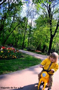 a pequeña mantiene el equilibrio en su motito Típica situación en los parques de Bucarest, media tarde