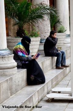 Mujer musulmana que para tapar sus ojos usa anteojos de sol, y todo el resto de su cuerpo tapado. Fuerte choque entre lo tradicional y lo moderno